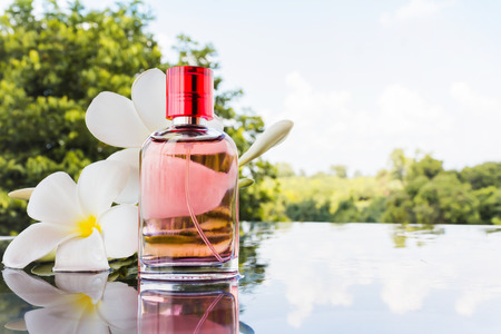 perfume: Single bottle of sweet pink fragrant perfume decorated with white flower and nature background