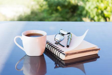 discreto: Classic White taza de caf� negro decorado con notas y bol�grafo con la naturaleza de fondo verde para el concepto de caf� por la tarde en simplemente estilo y tiempo de relax Foto de archivo