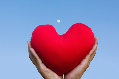 invigorate: Isolated two hands gently raise and hold red heart with love and respect with background of sky  for valentine or take care with love concept idea