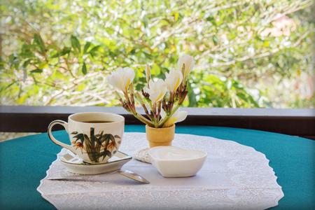 tarde de cafe: Classic White taza de café negro decorado con flores en el fondo verde de la naturaleza para el concepto del café de la tarde en estilo sencillo y relajarse tiempo