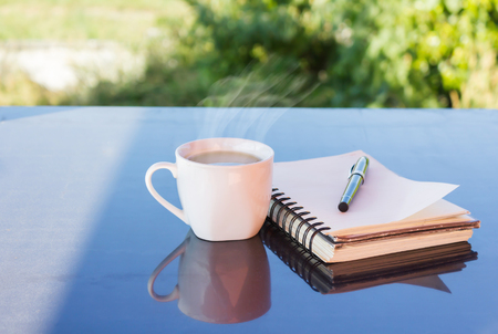tarde de cafe: Classic white cup of black coffee decorated with note and pen with green nature background for concept afternoon coffee in simply style and relax time
