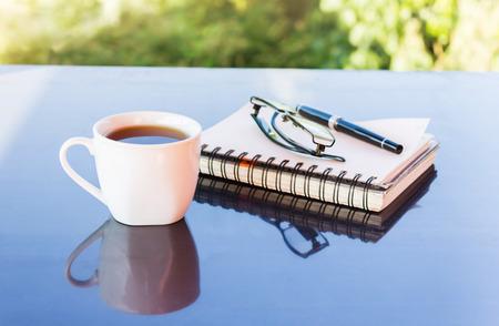 tarde de cafe: Classic White taza de café negro decorado con notas y bolígrafo con la naturaleza de fondo verde para el concepto de café por la tarde en simplemente estilo y tiempo de relax Foto de archivo