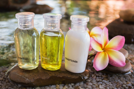 shampoo bottle: Mini set of bubble bath and shower gel decorated in zen style with pebble rock and flower with relaxing mood
