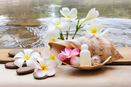Mini set of bubble bath and shower gel decorated in sea conch shell decorated with pebble rock and flower with water background