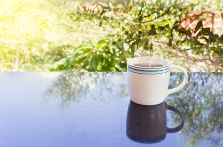 prudent: Classic white cup of black coffee on green nature background for concept afternoon coffee in simply style and relax time