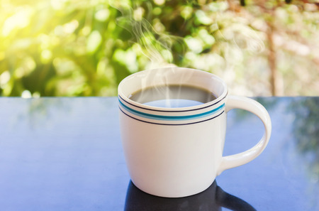 tarde de cafe: Classic white cup of black coffee on green nature background for concept afternoon coffee in simply style and relax time