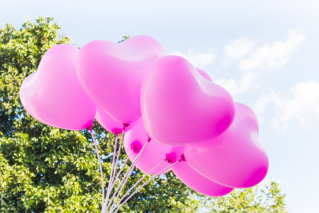 mild: Group of lovely pink heart pattern balloons on clear light blue sky with tree bush background Stock Photo