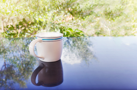 discreto: Classic white cup of black coffee decorated with flower on green nature background for concept afternoon coffee in simply style and relax time