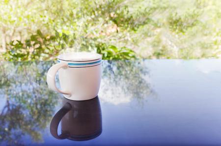 afternoon cafe: Classic White taza de café negro decorado con flores en el fondo verde de la naturaleza para el concepto del café de la tarde en estilo sencillo y relajarse tiempo