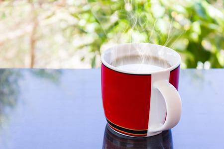 tarde de cafe: taza roja clásica de café negro sobre fondo verde de la naturaleza para el concepto del café de la tarde en estilo sencillo y relajarse tiempo