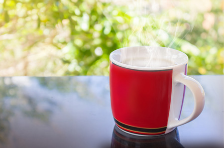 discreto: taza roja clásica de café negro sobre fondo verde de la naturaleza para el concepto del café de la tarde en estilo sencillo y relajarse tiempo