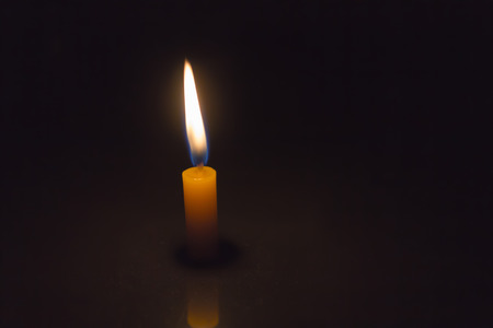 lighted: Single simply candle lighted in the dark background Stock Photo