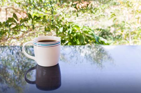 tarde de cafe: Classic White taza de café negro sobre fondo verde de la naturaleza para el concepto del café de la tarde en estilo sencillo y relajarse tiempo