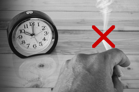 disallow: (Black and white colour tone) cigarette in hand and alarm clock, Your time your life concept