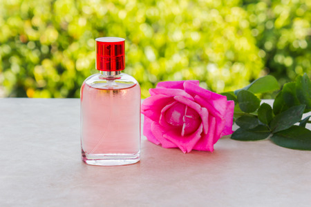 eau de perfume: Bottle of sweet pink fragrant perfume decorated with pink rose and nature background