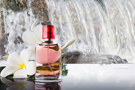 eau de perfume: Single bottle of sweet pink fragrant perfume decorated with white flower and waterfall background