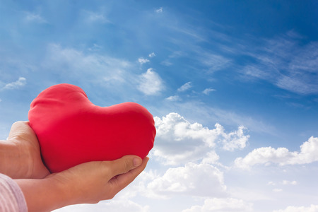 gently: Romantic lovely valentine concept with hand gently raise up red heart on blue sky background Stock Photo