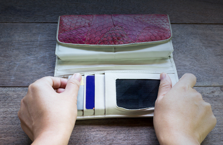 billfold: Hands pull credit card out of wallet