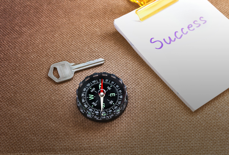 imply: compass with text success in business concept and key background