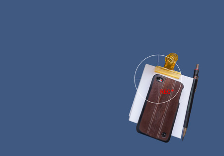 secretly: Secretly video streaming moblie phone with pencil on plain blue background
