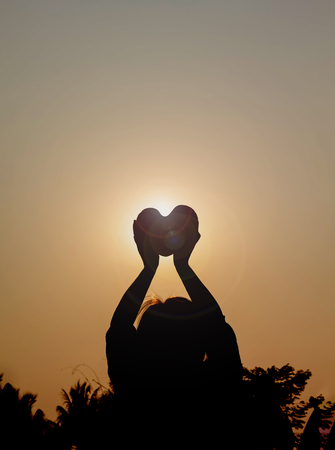 sincerely: Silhouette back of women raise heart with love and respect to sky on twilight sunlight background Stock Photo