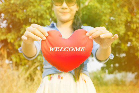 gently: Women hand gently hold red heart with text welcome on blurred wild grass flower field and tree background