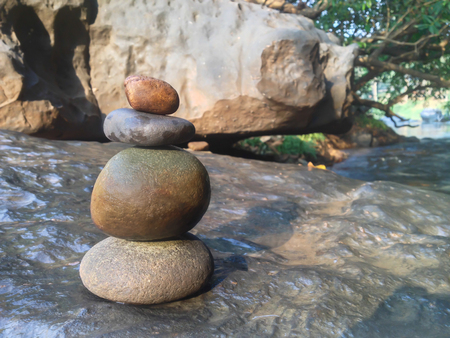 superimposed: Superimposed waterfall pebble rock arranged on big stone at waterfall background with copy space