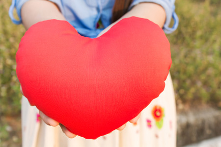 gently: Women hand gently hold red heart with love, careness and restpect with copy sapce Stock Photo