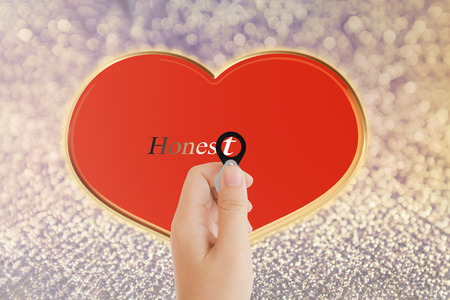 noteworthy: Isolated hand with lens and text honest with heart shape on bokeh background with copy space, concept idea of focus on sincere