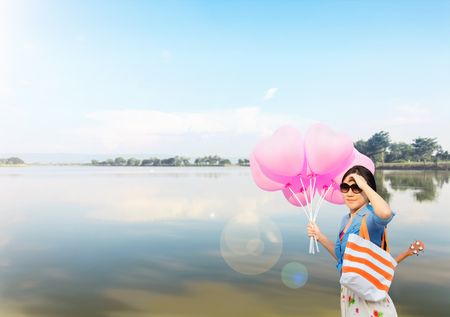 cary: Asian women wearing sunglasses with ukulele in summer bag carried on the shoulder taking heart shape pink balloons in hand standing infront of lake with mountain sky line pupblic park background