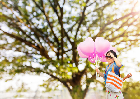cary: Asian women wearing sunglasses with ukulele in summer bag carried on the shoulder taking bunch of heart shape pink balloons in hand standing infront of blurred big tree and lake in pupblic park view fresh happy morning sunny background Stock Photo