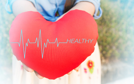 healthier: Women presenting red heart with pulse or heart beat and text healthy on for health background with copy space