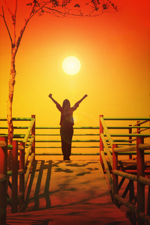 freely: Women shadow stand and raising two arm to sky freely at top view point sightseeing, freedom feeling in twilight colour concept with copy space Stock Photo