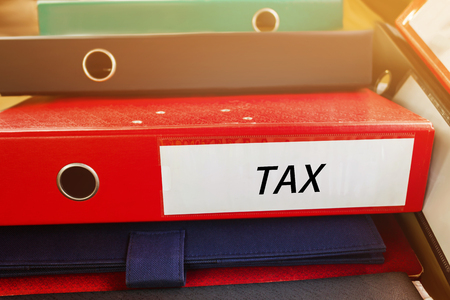 levy: Pile up document file or binder with text tax at spine for business concept background
