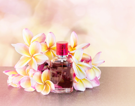 eau de perfume: Single bottle of sweet pink fragrant perfume with pink flower plumeria or frangipani and sweet abstract background