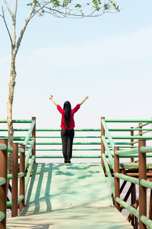 freely: Women stand and raising two arm to sky freely at top view point sightseeing, freedom feeling concept with copy space