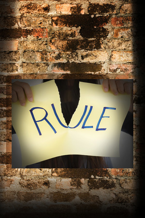 unorthodox: People hand hold torn sign with tex rule behind old brick wall Stock Photo