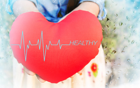 beat women: Women presenting red heart with pulse or heart beat and text healthy on for health background with copy space