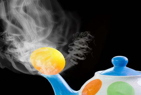 teakettle: Abstract concept idea gold egg on teakettle and hot steam on smoke and black background with copy space
