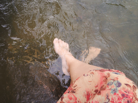 crystalline: Dreamy fantasy colour lifestyle, Women in flowers dress sit and dip feet in crystalline stream, summer relaxing feeling