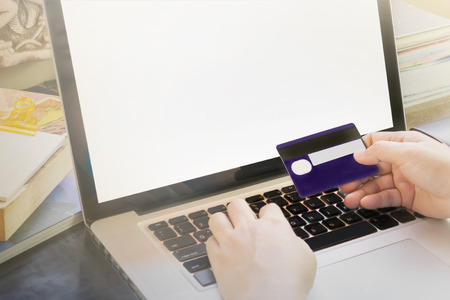 expedient: People hands hold credit or debit card infront of notebook for internet working