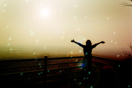 liberal: Silhouette back of women raising two arm embracing to sunlight and world in freedom concept Stock Photo