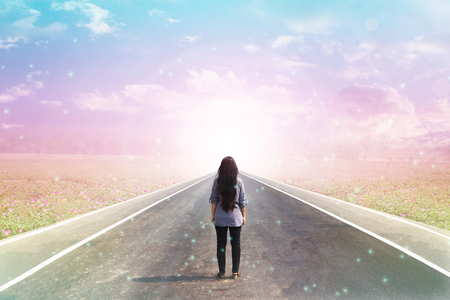 lensflare: Back or rare of women standing on pavement road with dreamy morning sunlight, flower field  and lensflare background with copy space, concept road to heaven Stock Photo