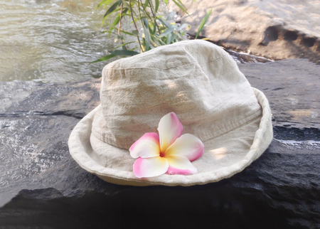 ourdoor: Hat with flower frangipani or plumeria on waterfall rock with river background and copy space