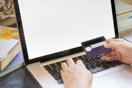 swiftly: People hands hold credit or debit card infront of notebook for internet working