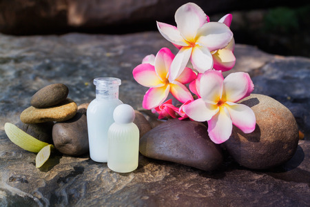 copy sapce: Mini set of bubble bath shower gel liquid with flowers and pebble on waterfall rock  with  relaxing feeling background and copy sapce