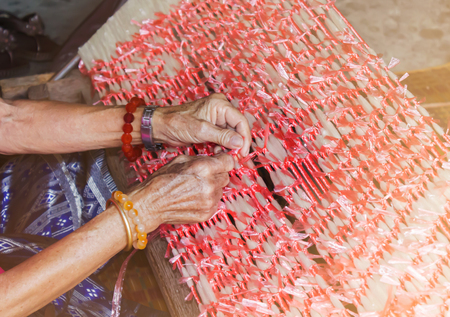 silk thread: Plastic rope tied on thread by old women hands, old folk way silk thread fasten step for silk cloth pattern or line design  before procedure of colour