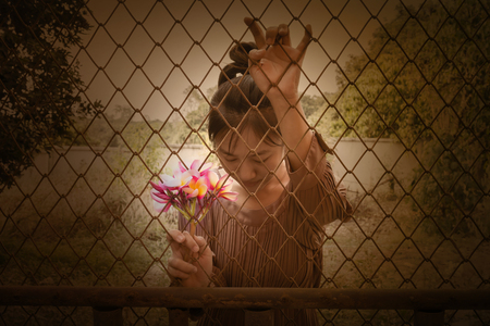 confine: Women and bunch of pink flowers frangipani in hand behind iron bar Stock Photo