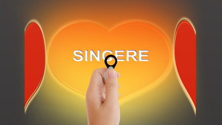 sincere: Beautiful big golden and red heart and text sincere with women hand taking focus lens
