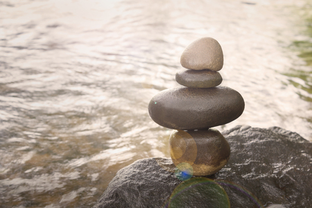 equivalence: Sepia nature picture of superimposed waterfall pebble rock arranged on big stone at waterfall background with copy space Stock Photo